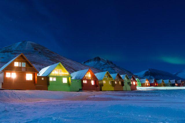 Polární záře nad domy na Špicberkách | foto: Shutterstock